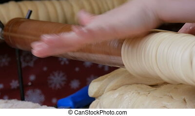 Female hands wrap the sticks of dough on a wooden stick. National Czech trdelnik sweet delicacy that is prepared on the street. Traditional Czech and Hungarian baking sweet bakery