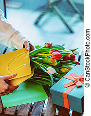 wrapping beautiful tulips in bag near gift box on wooden table