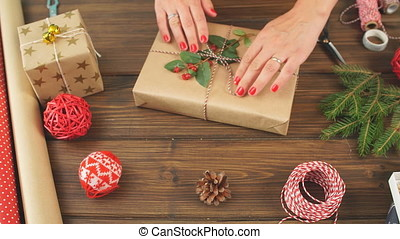 Female hands wrapping Christmas gift in craft ecological...