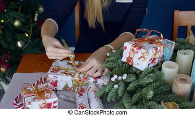 Female hands wrapping christmas presents - Close-up of...