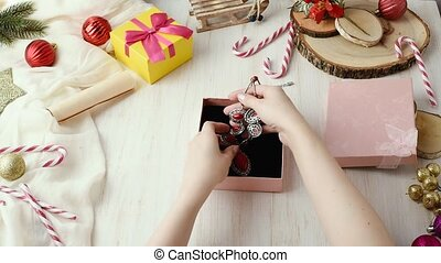 Female hands wraps up gift jewelry necklace and puts in a...