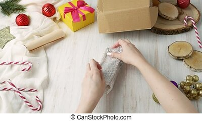 Female hands wraps up gift toy sledge in Bubble wrap and...