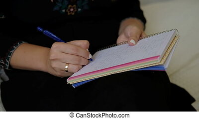 Female hands write a letter holding a notebook on their lap.