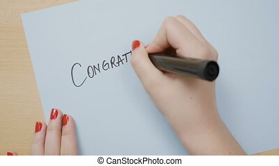 Female hands writing congratulations on a blue paper using a black marker
