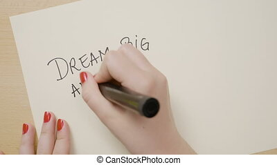 Female hands writing dream big and dare to fail exclamation point motivational quote on a white paper with a black marker