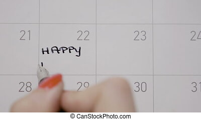 Female hands writing happy birthday with capital letters on calendar on 22 of the month using a black pen