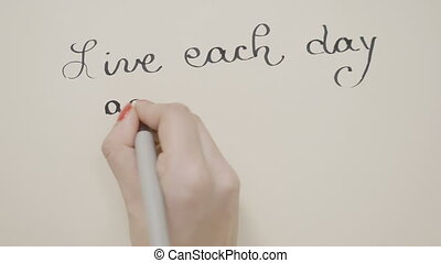 Female hands writing inspirational message live each day as...