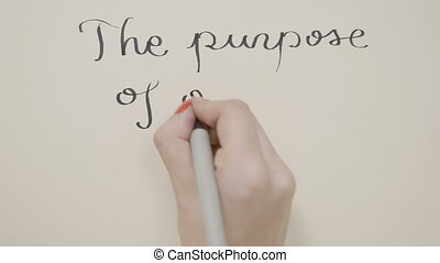 Female hands writing motivational message the purpose of our...