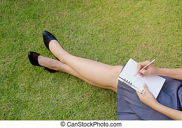 Female hands writing on notebook in park