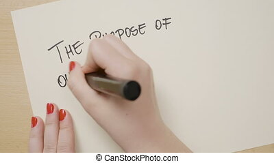 Female hands writing the purpose of our lives is to be happy motivational quote and drawing a smiley face on a white paper with a black marker