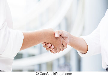 Female handshake with blurred white building