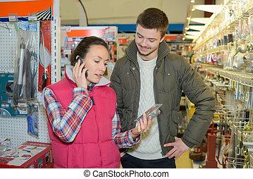 female hardware store employee advising customer