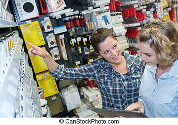 female hardware store worker helps to choose