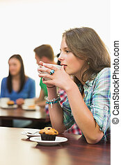 Female having coffee and muffin at  coffee shop