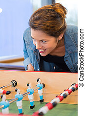 female having fun together playing table football