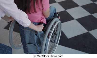 Female helper riding disabled woman sitting on wheelchair in...