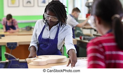 Female High School Student Building Guitar In Woodwork Lesson