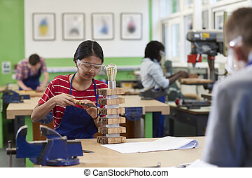 Female High School Student Building Lamp In Woodwork Lesson