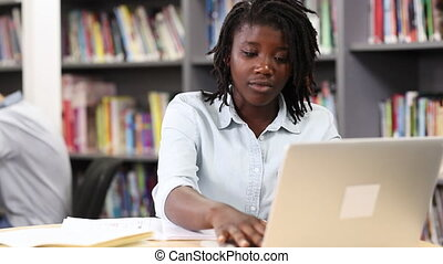 Female High School Student Working At Laptop In Library