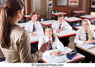 school teacher teaching in classroom - female high school...