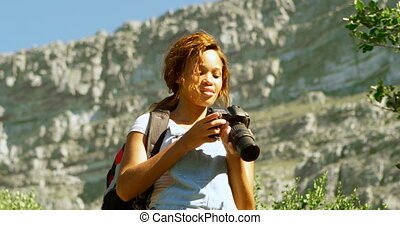 Female hiker clicking photos with digital camera 4k - Female...