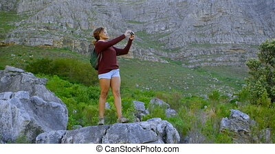 Female hiker clicking photos with vintage camera 4k - Female...