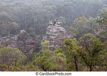 Female hiker in Blue Mountains on top of pagoda in mist and fog