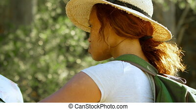 Female hiker looking at map in countryside 4k - Rear view of...