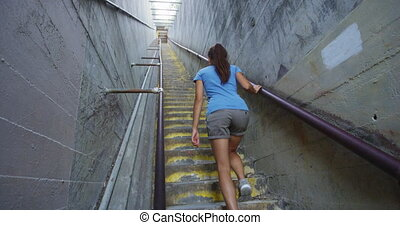 Female hiker moving up steps at Diamond Head State Monument. Young woman is wearing casuals during vacation. She is climbing staircase amidst concrete walls at famous landmark in Oahu.