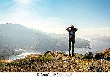 Female hiker on top of the mountain enjoying valley view, Ben A'an, Loch Katrina, Highlands, Scotland, UK