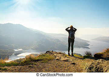 Female hiker on top of the mountain enjoying valley view,...
