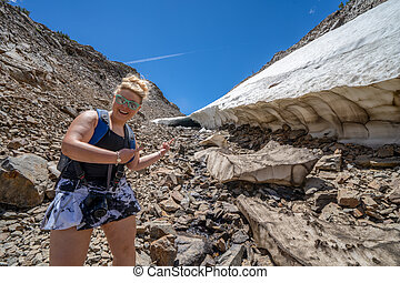Female hiker points and smiles at a large ice cave along a trail of scree and talus along 20 Lakes Basin in the Eastern Sierra Nevada Mountains of California