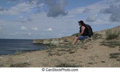 Female hiker resting on foreland by sea, arms outstretched....