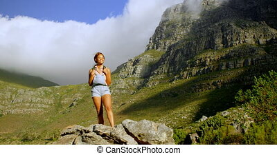 Female hiker standing on a rock 4k - Female hiker standing...