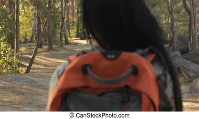 Female hiker turns around at the forest