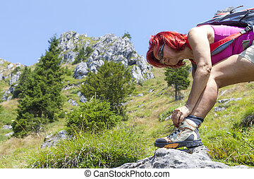 Female hiker tying boot laces