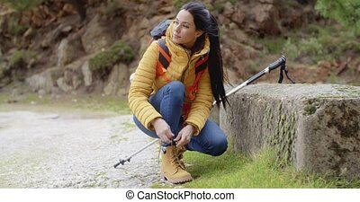Female hiker tying her laces on a sturdy pair of hiking...