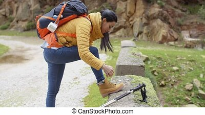 Female hiker tying her laces
