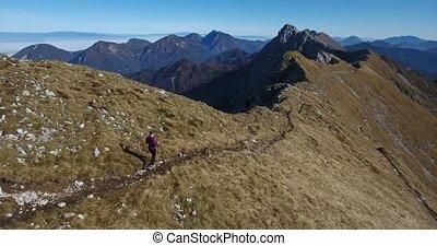 Female hiker walking a mountain ridge. Grass covered slopes.