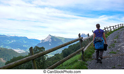 female hiker walking along a country road with a great view of a mountain landscape