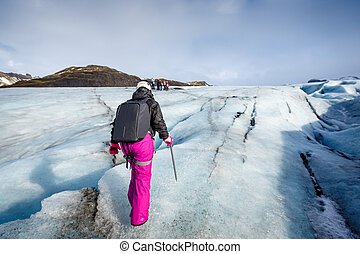 Female hiker walking on glacier at Solheimajokull, Iceland