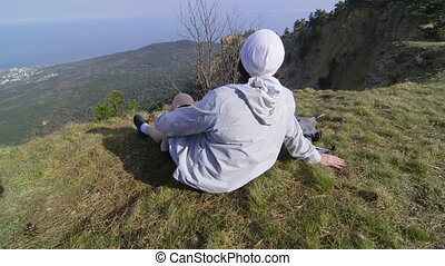 Female hiker with backpack enjoying the view from top of mountain