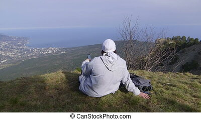 Female hiker with smartphone at mountain top
