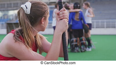 Side view close up of a teenage Caucasian female hockey player holding her hockey stick and kneeling on the pitch after losing the match, in the background the winning team in a huddle celebrating their victory, slow motion