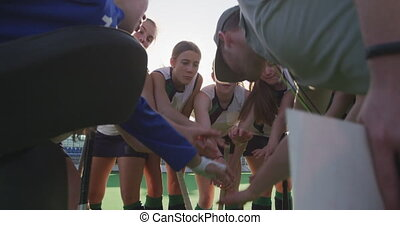 Female hockey players forming hand stack on the field - Side...