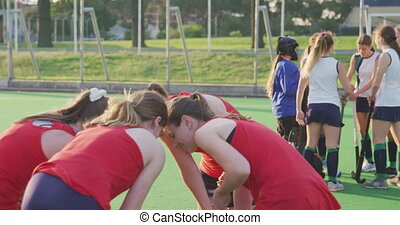 Side view of a teenage Caucasian female hockey team in a huddle on the pitch before a match at a sports stadium, players from the other team standing and talking in the background, slow motion