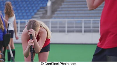 Side view close up of a teenage Caucasian female hockey player holding her hockey stick and standing on the pitch after losing the match, slow motion