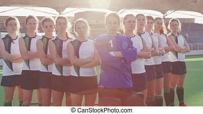 Female hockey players standing in a row with arms crossed