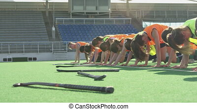 Side view of a Caucasian male coach instructing a teenage Caucasian female hockey team training on the pitch, doing exercises in a line, with their hockey sticks on the ground in front of them, backlit by sunlight, slow motion