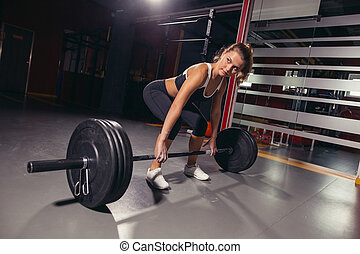 Female holding a barbell in her hands.